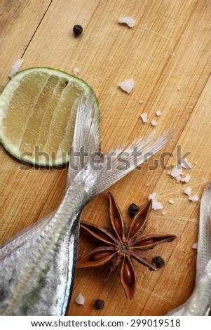 Fresh raw fish ,lemon ,salt ,star anise and pepper - stock photo
