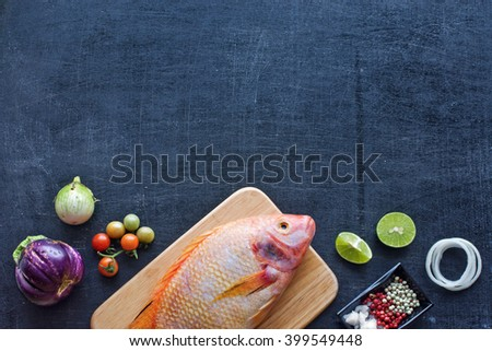 Fresh raw fish (Nile tilapia) with herbs and spices. Farm vegetables (eggplant, cherry tomato, onion). Dark background. Copy space.  - stock photo