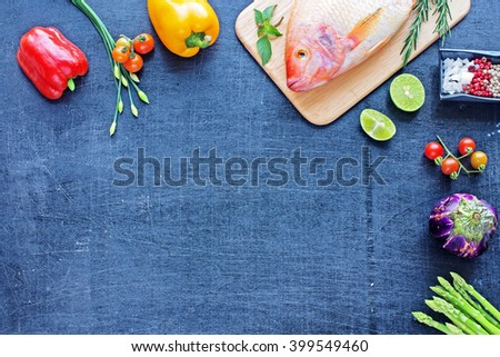 Fresh raw fish (Nile tilapia) with vegetables, herbs and spices on a dark background. Top view. Space for text. - stock photo