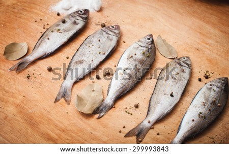 fresh raw fishes with spices on a cutting wooden board