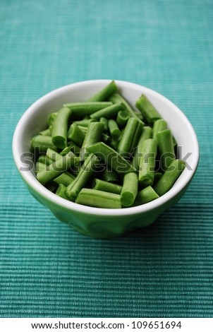 Fresh raw green beans in a ceramic bowl on green fabric gackground - stock photo