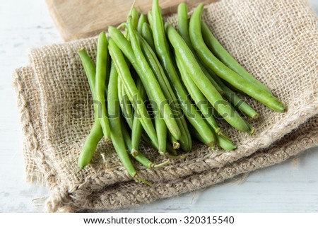 Fresh raw green beans on jute cloth - stock photo