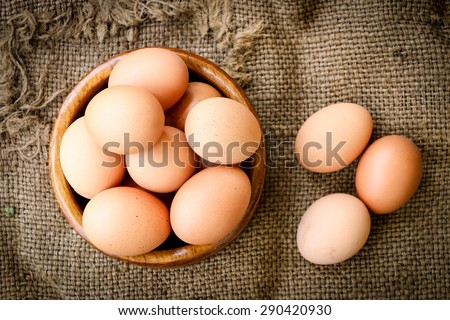 Fresh raw group of eggs put on old sack - stock photo