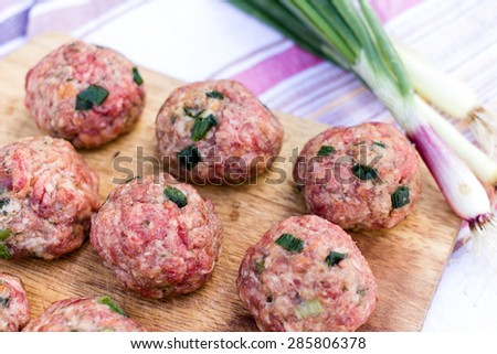 Fresh Raw Homemade Meatballs on Wooden Kitchen Desk with Fresh Green Onion. - stock photo