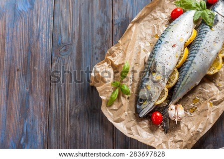 Fresh raw mackerel with lemon, tomatoes and spices on parchment. Preparing to bake - stock photo