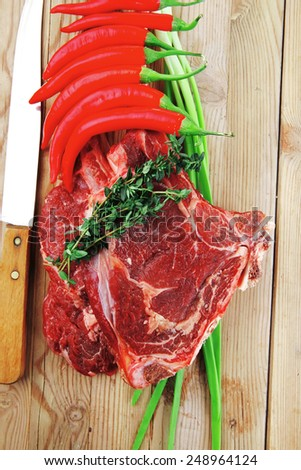 fresh raw meat : fresh red beef ribs with thyme , red chili pepper , and green onion on wooden board - stock photo