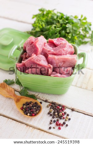 Fresh raw meat in bowl on white table with whole pepper, oil, herbs. Selective focus. - stock photo
