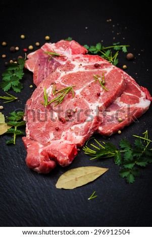 Fresh raw meat on black board with spices and herbs - stock photo