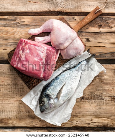 fresh raw meat products on wooden table - stock photo