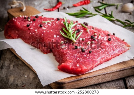 fresh raw meat steak on a cutting board with rosemary and pepper on rustic background - stock photo