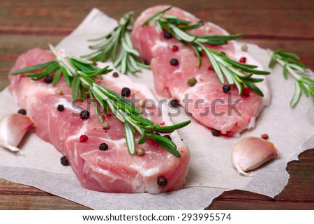 fresh raw meat with rosemary and pepper. - stock photo