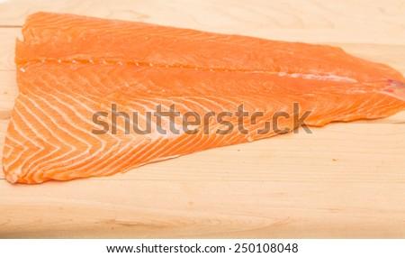 Fresh, raw piece of atlantic salmon on a wood cutting board - stock photo