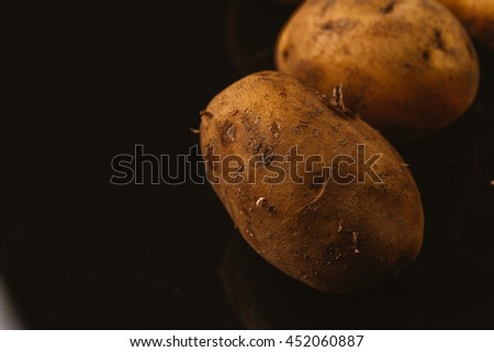 Fresh raw potatoes on a black background.