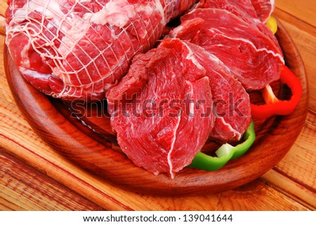 fresh raw red meat on wooden table - stock photo