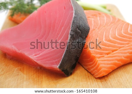 fresh raw salmon and tuna fish  pieces on wooden plate isolated on white background - stock photo