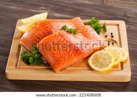 Fresh raw salmon fillet on cutting board - stock photo