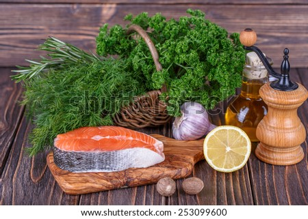 Fresh raw salmon fish steaks with fresh herbs on wooden background - stock photo
