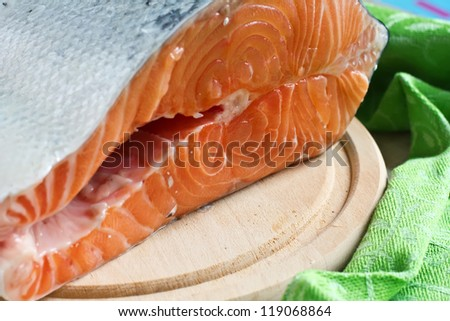 Fresh raw salmon on cutting board on wooden  background. Selective focus.