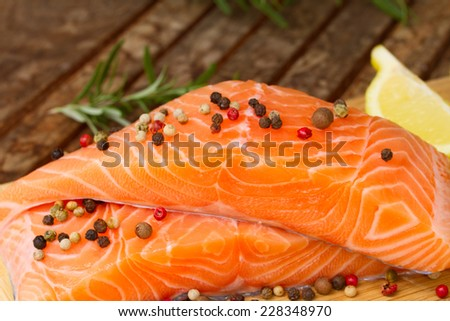 fresh raw salmon steaks on wooden table with spices  close up - stock photo