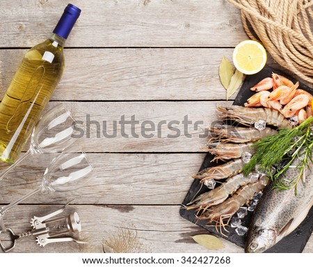 Fresh raw sea food with spices and white wine on wooden table background. Top view with copy space - stock photo