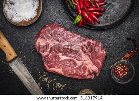 fresh raw steak with red pepper salt pan carving knife on a dark rustic background top view close up - stock photo