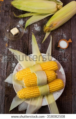 fresh raw sweet corn on rustic wooden background - stock photo