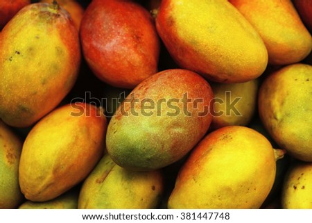 fresh raw sweet mango heap as background on market - stock photo