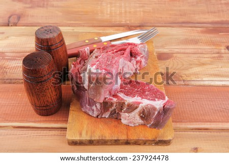 fresh raw uncooked beef fillet mignon entrecote on board prepared for cooking on wood table wtih cutlery and castors - stock photo