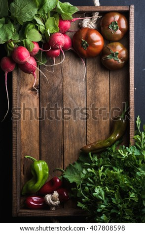 Fresh raw vegetable ingredients for healthy cooking or salad making in rustic wooden tray over black background, top view, copy space. Diet or vegetarian food concept. Vertical - stock photo