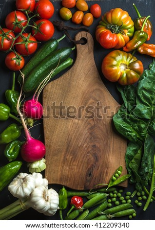 Fresh raw vegetable ingredients for healthy cooking or salad making with dark wooden cutting baoard in center, top view, copy space. Diet or vegetarian food concept. - stock photo
