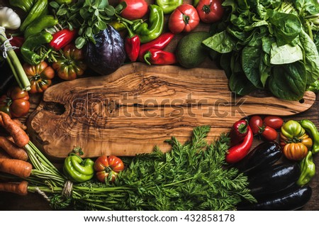 Fresh raw vegetable ingredients for healthy cooking or salad making with rustic olive wood board in center, top view, copy space. Diet or vegetarian food concept, horizontal - stock photo