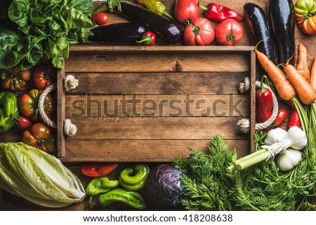 Fresh raw vegetable ingredients for healthy cooking or salad making with rustic wooden tray in center, top view, copy space. Diet or vegetarian food concept, horizontal composition