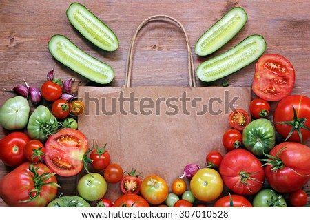 Fresh red and green tomatoes lie on a paper package, segments of cucumbers on a table, the top view. Tomatoes mature and immature. A still life with vegetables. - stock photo