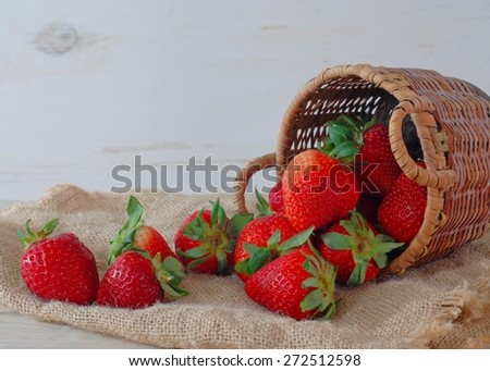 Fresh, red and ripe strawberries and a basket with a rustic, natural background. The strawberries are topped with green stems and leaves. Horizontal composition. Summer fresh message.  - stock photo