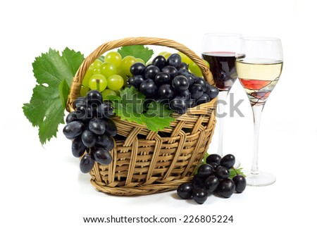 Fresh Red and White Grapes with Green Leaves in Wicker Basket and Two Wine Glass Cups Filled with Red and White Wine Isolated on White Background - stock photo