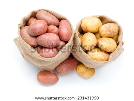 Fresh red and white potatoes crop in burlap bag - stock photo