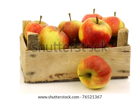fresh red and yellow apples in a wooden box on a white background