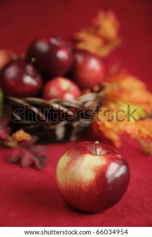 fresh red apple with a basket full of red apple in background - stock photo
