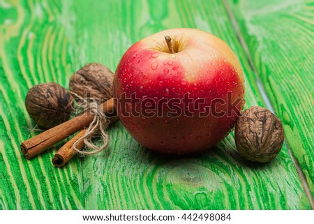 fresh red apple with water drops near cinnamon sticks with rope and walnuts on bright textured green wooden background