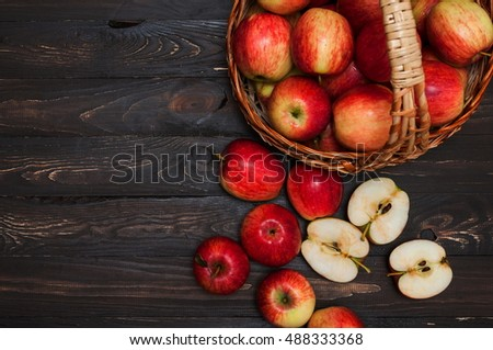Fresh red apples in the basket and half apple on a dark wooden background with space for text. Detox diet or healthy eating concept.
