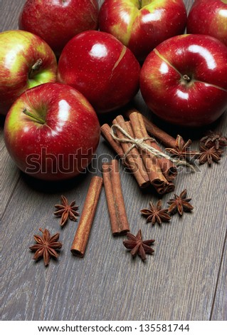 Fresh red apples with cinnamon and anise, on the wooden table