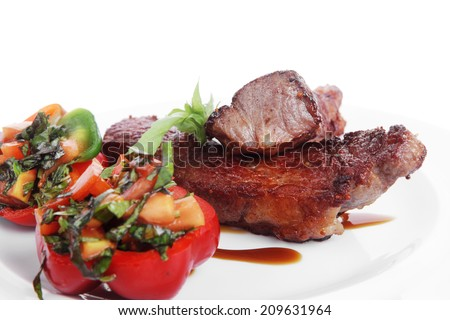 fresh red beef meat steak barbecue garnished vegetable salad and basil  in half of pepper bell on white plate isolated over white background - stock photo