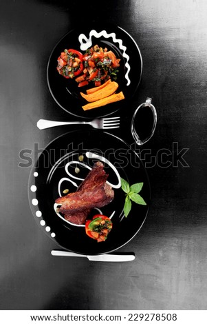 fresh red beef meat steak barbecue garnished vegetable salad sweet potato and basil on black plate over black wooden table with bbq sauce in sauceboat high resolution - stock photo