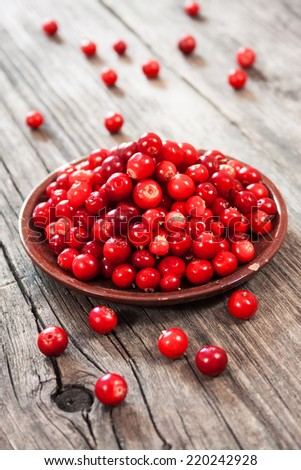 fresh red berries on wooden table - stock photo