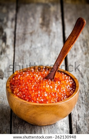 fresh red caviar in a wooden bowl with a spoon on a rustic background - stock photo