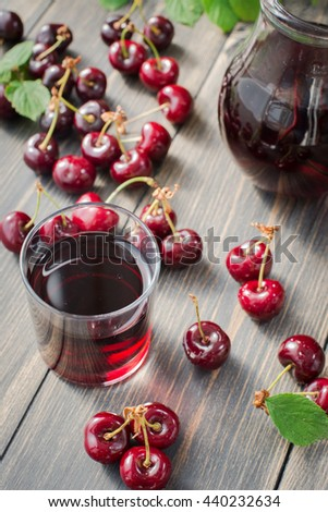 fresh red cherries and cherry juice on an old wooden table with green leaves, rustic style - stock photo
