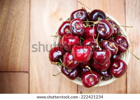fresh red cherries on a wooden table background - stock photo