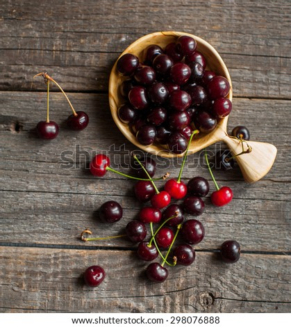 fresh red cherry berries on vintage wooden background - stock photo