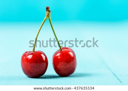 Fresh Red Cherry Fruit On Turquoise Background - stock photo
