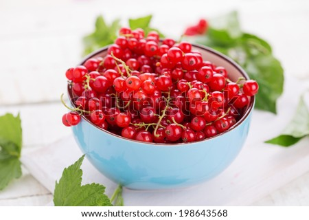 Fresh red currant in bowl on white wooden background. Selective focus. - stock photo